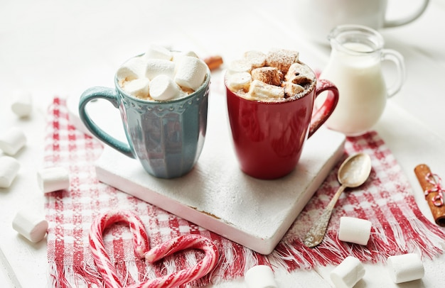 Christmas cookies, milk, cocoa, marshmallows, candies on a white plate by the window