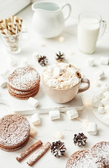 Christmas cookies, milk, cocoa, marshmallows, meringue plate by the window
