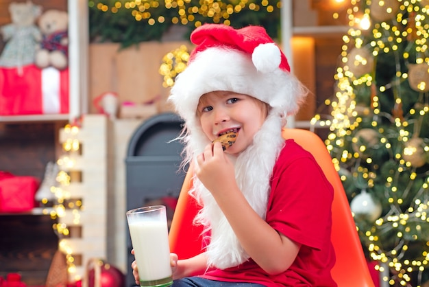 Christmas cookies and milk. little santa claus kid with beard and mustache. santa in home. santa