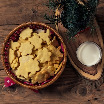 Christmas cookies and milk for santa clause on wood .