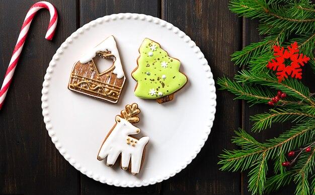 Рождественское печенье на тарелке на темном деревянном фоне