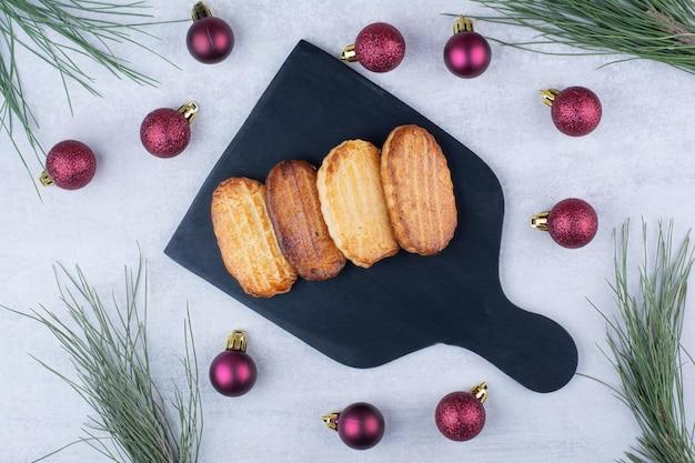 Рождественское печенье на черной тарелке с шарами. фото высокого качества