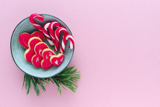 Christmas cookies on a plate with spruce branches on pink