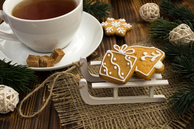 Christmas cookies on the sledges and tea on the wooden background