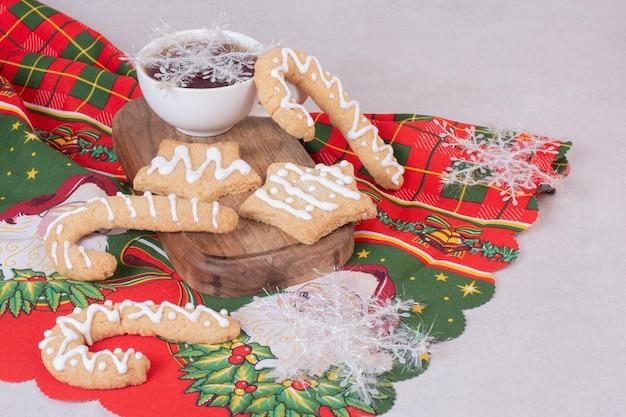 Biscotti di natale con tè aromatico in tazza sul tavolo bianco.