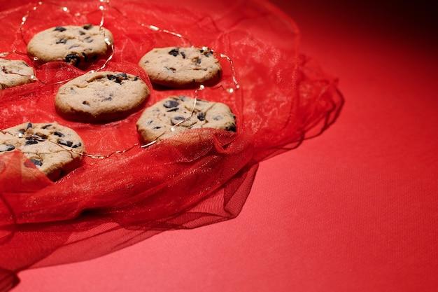 赤い新年の背景にチョコレートとクリスマスクッキー