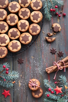Christmas cookies with chocolate star pattern on cooling rack with spices and decorated fir twigs