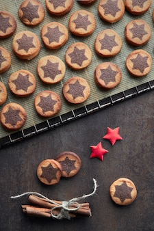 Christmas cookies with chocolate star pattern on cooling rack with spices