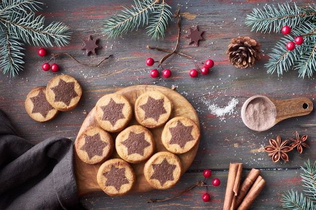 Christmas cookies with chocolate star pattern with choco stars, cinnamon and decorated fir twigs