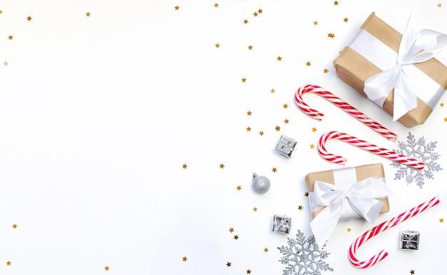お祝いの装飾と白い背景の上の贈り物とクリスマスのクッキー