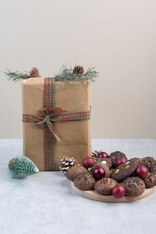 Biscotti di natale con confezione regalo, palline e pigne. foto di alta qualità