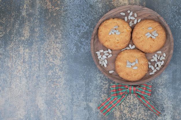 リボンで飾られた木の板に種が付いたクリスマスクッキー。高品質の写真