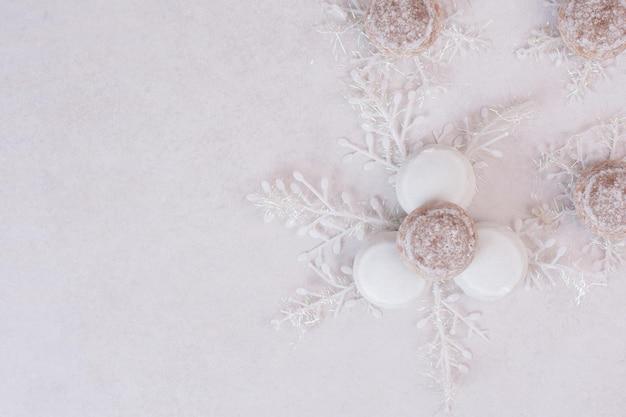 白いテーブルの上の雪片とクリスマスクッキー。