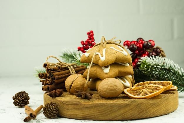 나무 커팅 보드에 향신료와 말린 오렌지를 넣은 크리스마스 쿠키를 닫습니다.