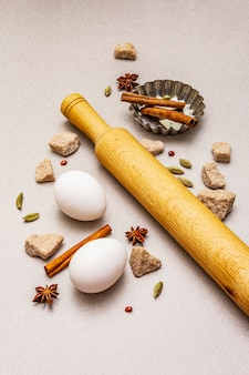 Christmas cooking , spices, eggs, brown lump sugar, cupcake baking dish and a rolling pin. light stone concrete