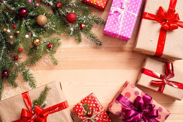 隅に飾られたモミの木の枝と周りのカラフルなプレゼントのあるクリスマスコピースペース