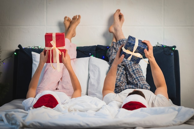 Christmas couple holding gifts in bed