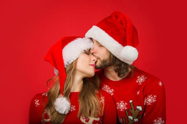 新年の帽子の関係の概念のクリスマスのカップルは、カップルの新年のキスの肖像画をクローズアップ