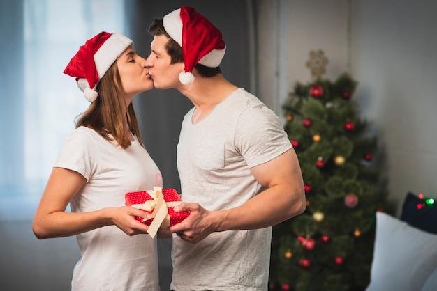 クリスマスのカップルが寝室でキス