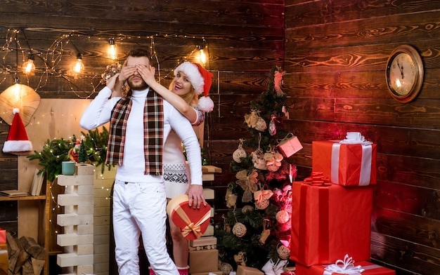 Christmas couple in love merry christmas and happy holidays lovely woman is closing her man eyes hap...