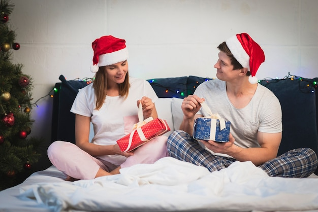 Christmas couple opening gifts in bed