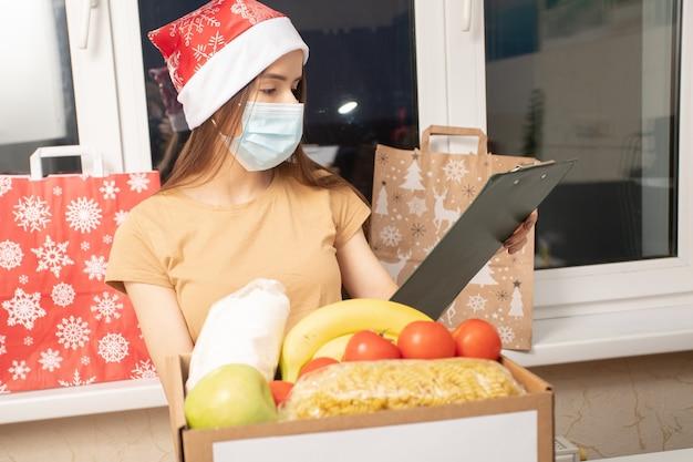 Молодая женщина-волонтер в медицинской маске упаковывает продукты и еду в коробку для пожертвований на рождество