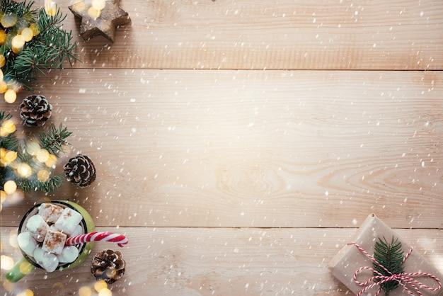 복사 공간, 크리스마스 및 새해 인사말 카드가 있는 나무 배경에 뜨거운 초콜릿, 나무 눈송이, 크리스마스 나무 가지가 있는 크리스마스 아늑한 프레임