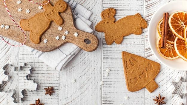 나무 표면에 생강 쿠키와 쿠키 몰드가있는 크리스마스 아늑한 표면