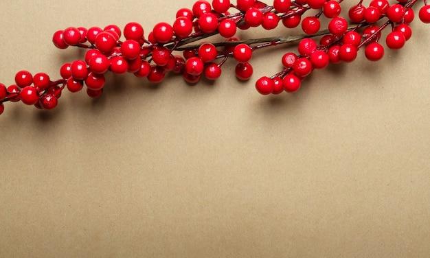 上部に赤いベリーやガマズミ属の木の枝が付いたテキストまたはコピースペースの場所が付いたクリスマスクラフトの茶色のバナー。