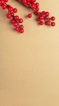 上部に赤いベリーやガマズミ属の木の枝が付いたテキストまたはコピースペースの場所が付いたクリスマスクラフトの茶色のバナー。垂直