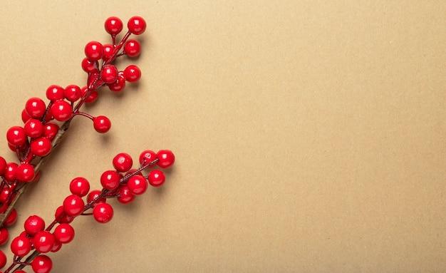 赤い果実やガマズミ属の木の枝でテキストまたはコピースペースのための場所とクリスマスクラフト茶色のバナー。