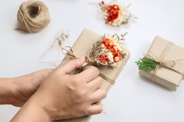 クリスマスクラフトの手作り趣味。ドライフラワーと松の葉でプレゼントを飾る女性の手。