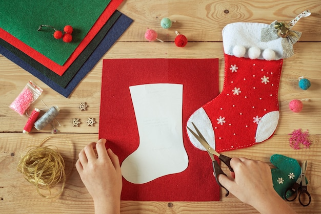 Christmas crafting, hands holding scissors and cutting the shape of christmas stocking