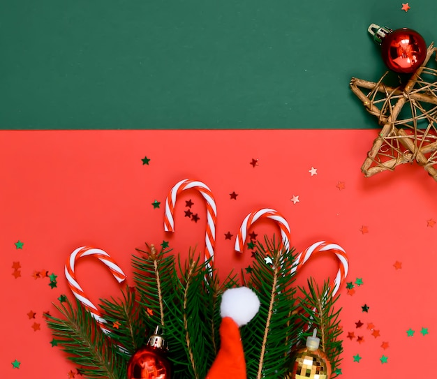 Christmas creative composition of a tree branch, santa hat, christmas balls, stars, on a red and green new year, winter concept. flat lay, top view, copyspace