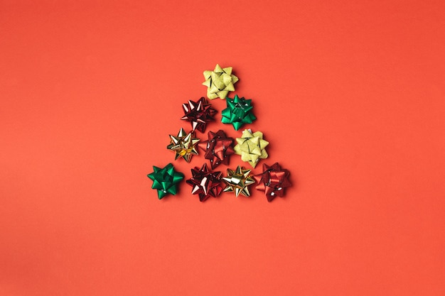 Christmas creative concept with bows in the form of christmas tree on red