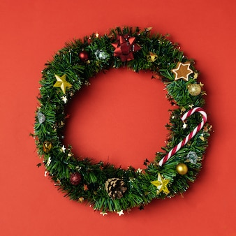 Christmas creative concept with christmas wreath from green tinsel with gingerbread cookie, candy cane and pinecone, stars