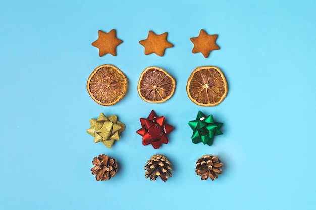 Christmas creative concept with gingerbread, dried orange, bows, ornaments, pinecone on light blue