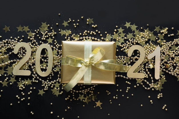 Christmas creative shiny banner of golden gift and date 2021 new year on black space