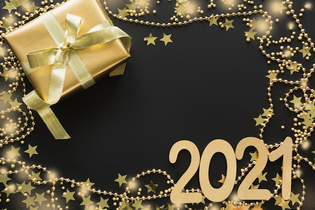 Christmas creative shiny border of golden beads, gift on black space with date 2021 new year