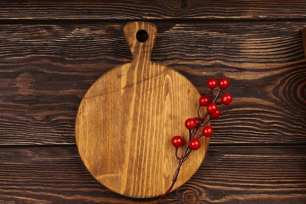 木製の背景にクリスマス料理のレイアウト。休日のテーブルメニューのクリスマスアイテムと木製のまな板。上面図、フラットスタイル。