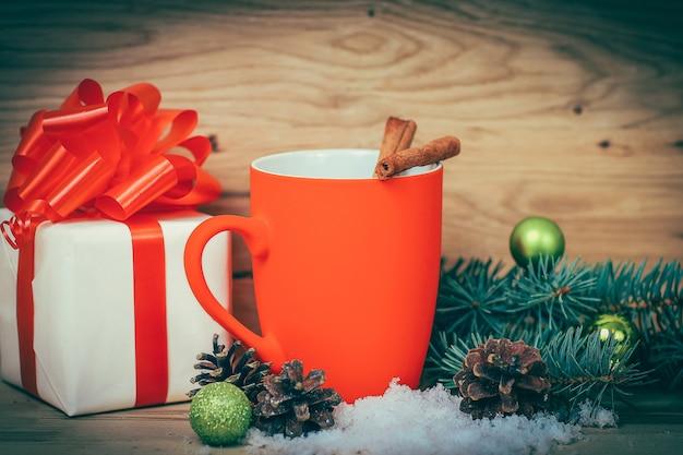 クリスマスカップと木製の背景にクリスマスプレゼント。コピースペースの写真