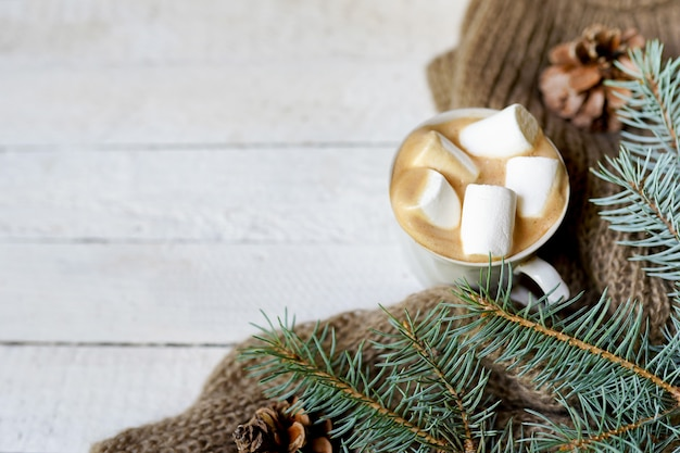 Christmas cup of coffee, scarf and green fir branches on white wood background,copy space