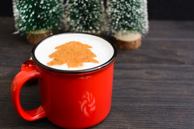 Christmas cup of coffee with fir tree. new year beverage on wooden table