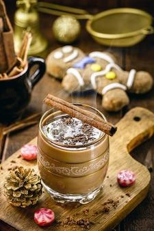 배경에 핫 초콜릿, 계피 스틱, 진저브레드 맨으로 장식된 크리스마스 컵