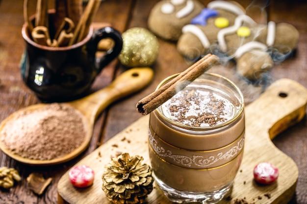 배경에 핫 초콜릿, 계피 스틱, 코코아, 진저브레드 맨으로 장식된 크리스마스 컵