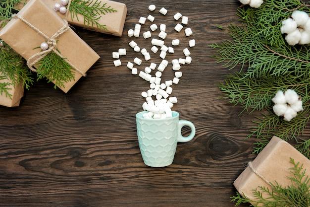 暗い木の板、トップビューでクリスマスカップ、マシュマロ、ギフトボックス