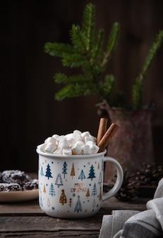 쿠키와 전나무가 있는 오래된 갈색 나무 테이블에 계피와 함께 카카오와 마시멜로의 크리스마스 컵. 새해 분위기. 전면보기