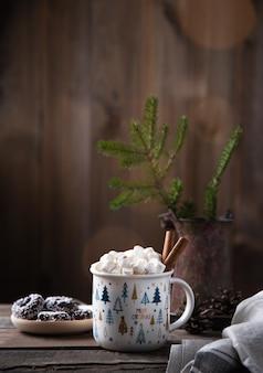 쿠키, 보케, 콘, 전나무가 있는 오래된 갈색 나무 테이블에 계피를 곁들인 카카오와 마시멜로의 크리스마스 컵. 새해 분위기. 전면 보기 및 복사 공간
