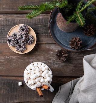 쿠키, 보케, 콘, 전나무가 있는 오래된 갈색 나무 테이블에 계피를 곁들인 카카오와 마시멜로의 크리스마스 컵. 새해 분위기. 평면도