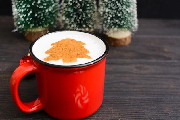 モミの木とコーヒーのクリスマスカップ。木製のテーブルに新年の飲み物